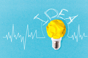 Wall Mural - crumpled yellow paper light bulb near to a cardiogram on a blue background with inscription idea