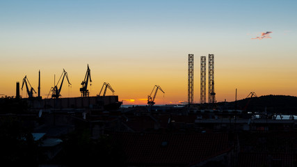 The panoramic view of shipyard cranes and structures silhouettes at sunset. Pula, Istria region of Croatia