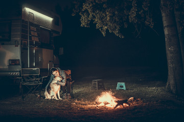 Woman hugging dog standing at camp fire with motorhome.