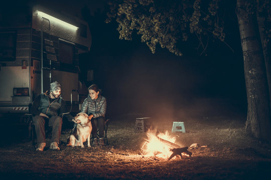 Couple on vacantion near campfire and motorhome