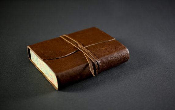 leather bound book on black background