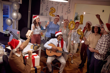 Happy multiethnic business group people have fun and dancing in Santa hat at Xmas party.