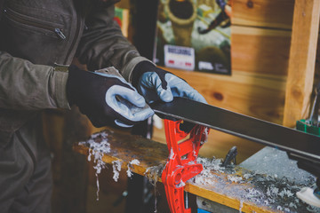 A male worker in a ski service workshop repairs the sliding surface of the skis. Close-up of a hand with a plastic scrapper for removing wax, removing new wax. Theme repair of ski curb