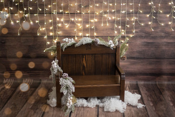 Christmas photo zone. Christmas decor. garland. the bench is decorated with spruce. artificial snow