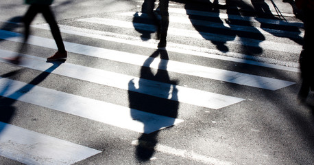 Fotomurales - Blurry zebra crossing with pedestrians making long shadows