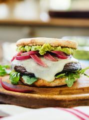 Portabella mushroom sandwich with Havarti cheese, red onions, arugula and guacamole