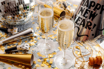 Happy new year celebration concept theme with close up on two glasses of champagne, disco ball covered in mirror, noise makers and party trumpets, confetti, beads and a cork on silver background