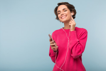 Beautiful dreamy girl in pink sweater holding cellphone in hand while happily listening music in earphones over blue background