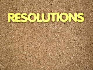 The word RESOLUTIONS in yellow letters on a cork board with copy space