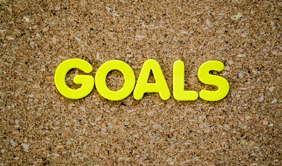 The word GOALS in yellow letters on a cork board with copy space