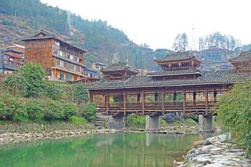 The Wooden Bridge of Qian Hu Miao Zai Village in morning mist , Guizhou province China.