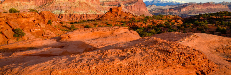 Sunset during golden hour in Southern Utah, sun warming red sandstone, cliffs, mountains, and mesa
