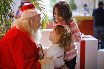 "Icelander Einar Sveinsson, dressed as Santa Claus, talks with children during the ""Villa Navidad"" Festival in San Salvador"
