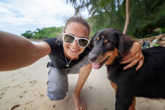 Young beautiful happy joyful girl woman having fun taking a selfie on a mobile phone with her dog on the beach along the sand