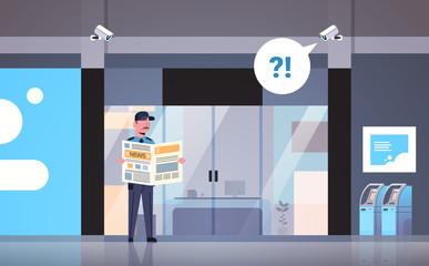 security guard man reading newspaper distracted at workplace entrance door business building exterior CCTV surveillance camera equipment flat horizontal