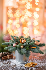 Christmas arrangement with Norwegian pine Nobilis and decorated with Christmas decor in a metal Cup. Garland bokeh on background. Christmas love. Dark wooden table sprinkled with snow