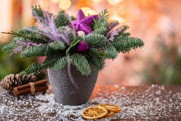 Christmas arrangement with Norwegian pine Nobilis and decorated with Christmas decor in a ceramic Cup. Garland bokeh on background. Christmas love. Dark wooden table sprinkled with snow
