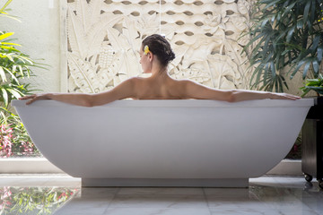 Portrait of a young woman relaxing in the bathtub, organic skin-care at the luxury hotel spa, wellbeing and self-care concept