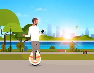 man ride electric mono wheel using smartphone guy modern personal transport outdoor nature city urban park cityscape sunset background horizontal flat