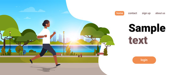 african american woman jogging outdoors modern public park girl headphones running sport activity concept cityscape sunset background horizontal copy space