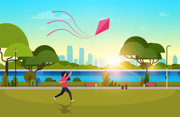 young woman launching kite outdoors modern public park girl playing wind toy holiday concept cityscape sunset background horizontal flat