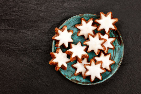 Christmas Zimtsterne, traditional German almond, chocolate and cinnamon star cookies, shot from the top on a dark background with copy space