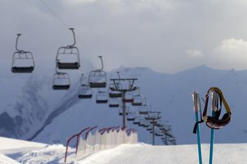 Snowy skiing slope, chair-lift and ski mask on ski poles