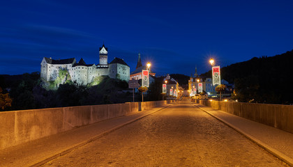 Panoramic, night view from a bridge on a Loket Castle (Hrad Loket, Burg Elbogen), impregnable castle on a massive rock, illuminated by street lamps. Tourist spot near to Karlovy vary, Czechia.