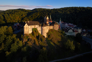 Aerial view on Loket Castle, Burg Elbogen, gothic style castle on a big rock against   green spruce forest, massive fortification illuminated by setting sun. Close to Karlovy vary, Czech republic