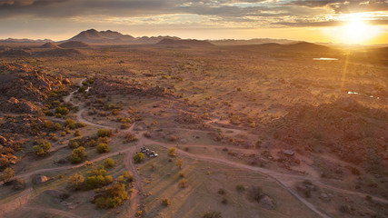Aerial photo of sunrise over rocky desert, long shadows and beautiful colors. Morning in vaste wilderness without people, close to Spreetshoogte Pass, Nauchas, Namibia.
