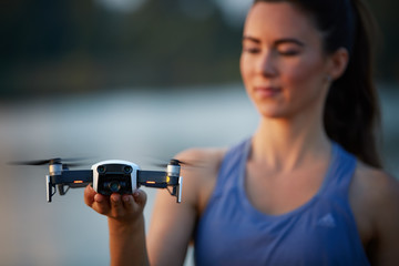 Young beautiful woman controls a white quadcopter by remote controller with a tablet. Focused on the drone, the pilot is out of focus. Teaching flying with a dron in summer nature.