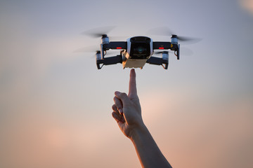 A small quadcopter model hovering in the air directly over a pointing finger against colorful evening sky. Young woman testing new technology.