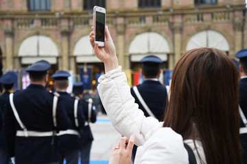 Young woman taking photo on her smartphone. On the background a man with military uniform. Bologna, Italy