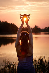 Young beautiful woman keeps a small white quadcopter over her head in hands against setting sun. Technology and woman.