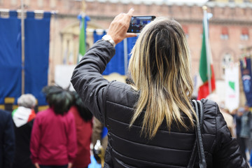 A blonde woman taking photo with her smartphone. On the background men with military uniform. Bologna, Italy