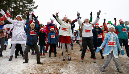Belarusians dressed as Santa Clauses and other Christmas characters warm up before taking part in the country's first Santa Run around a lake in Minsk