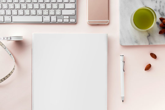 Creative flat lay workspace with minimal style. Modern desk with computer, smartphone, magazine, notebook, pencil, tapeline, almonds and a glass of green tea on a pastel pink background, top view
