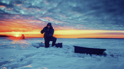 Fisherman on the background of the sunset on the winter lake. Ice fishing.