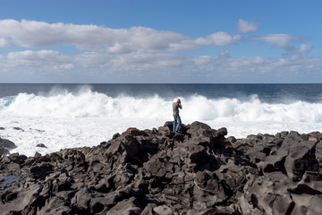 Old man photographs big waves on the coast of Lanzarote. Canary Islands