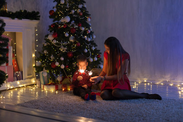 mother and son celebrate the new year at a Christmas tree with gifts