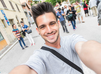 Handsome man smiling on the camera taking a selfie walking in the city