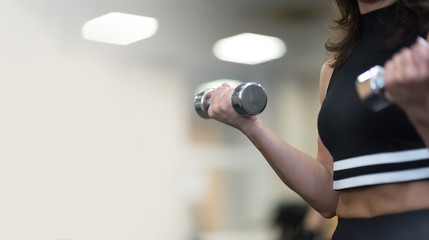 young woman and personal trainer with dumbbells flexing muscles in gym. copyspace