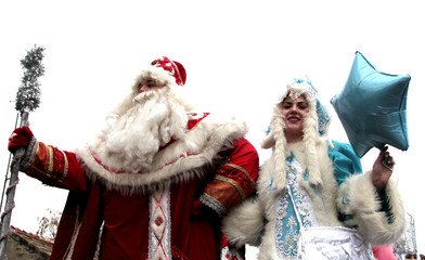 A man dressed as Father Frost and a woman dressed as his granddaughter Snegurochka attend a New Year festival in Yevpatoria