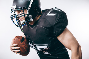 Emotional American football centre forward player in black protective uniform throwing a ball, isolated over white background