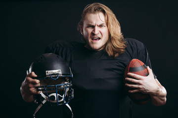 Angry american football coach holding football ball over isolated background, ready to fight for win, shouting with anger and excitement, Sport and Emotions concept
