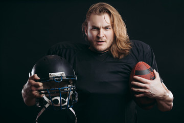 American football team captain posing in motion with ball isolated on the black background, his face radiates aspiration for victory.