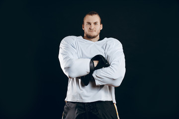 Portrait of ice-hockey player in white headgear and defensive suit looking at camera with folding crossed hands against black background.
