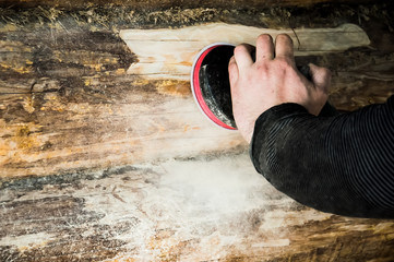a man cleans the skins of a log with a grinding machine in a wooden house