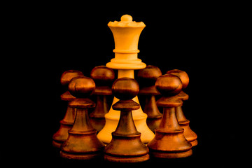 Under siege. White Queen beset by black enemy pawns with sense of no escape, standard chess wooden piece on black background