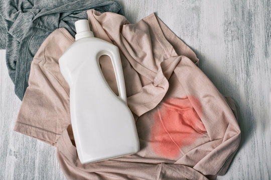 Clothes with stains and a bottle of detergent. Top view